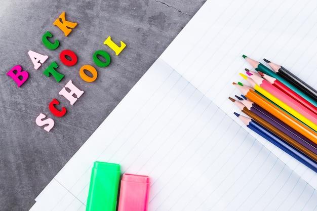 La disposition des fournitures scolaires sur un fond gris foncé