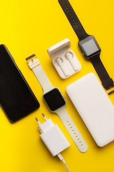 Disposition des gadgets technologiques isolés sur fond jaune