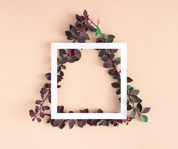 Disposition géométrique faite de branches avec des feuilles vertes en forme de triangle et cadre de carte en papier.