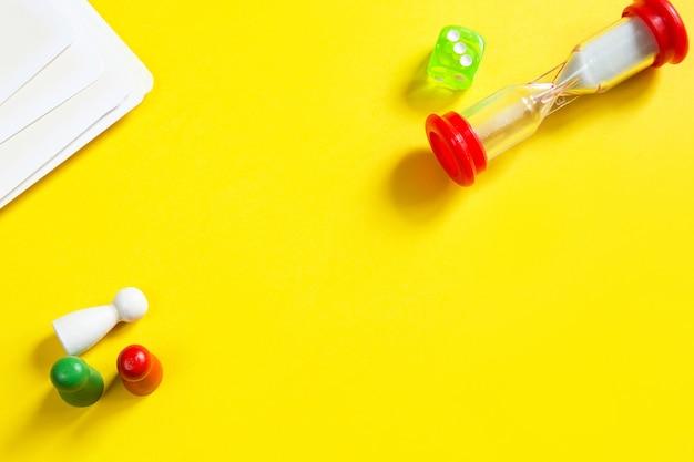 Disposition de jeux de société sur fond jaune, dés, jetons, sablier.