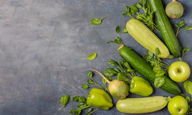 La disposition des légumes verts sur un fond sombre.