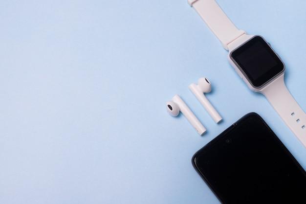 La disposition de la montre et du téléphone sur fond bleu appareils électroménagers et électronique