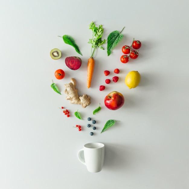 Disposition de la nourriture créative avec des fruits, des légumes et des feuilles sur un mur de table en marbre brillant avec une tasse de thé. concept de boisson saine minimale. mise à plat.