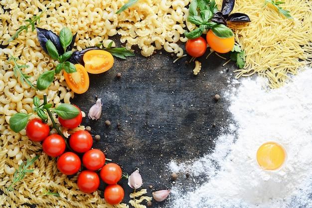 Disposition des pâtes et des légumes sur un mur sombre