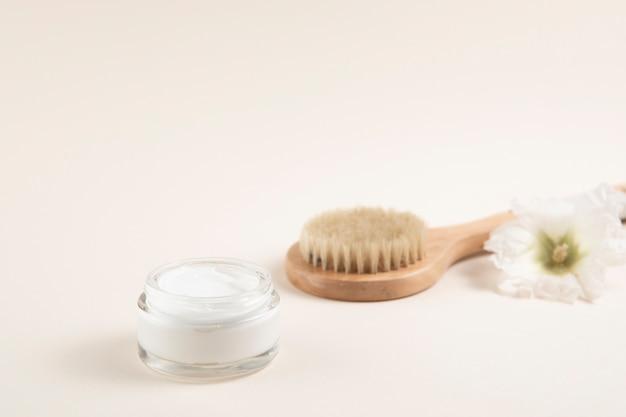 Disposition de pinceaux crème et cheveux avec fond uni