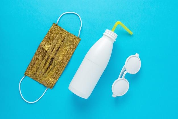 Disposition de la plage d'été avec des lunettes de soleil bouteille blanche et masque médical