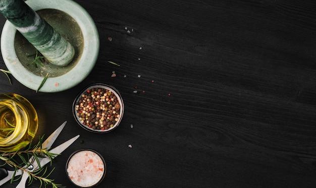 Disposition des produits pour la cuisson des assaisonnements dans un mortier en marbre. composition avec sel de mer, romarin, huile d'olive et divers types de poivre sur un fond en bois foncé, vue de dessus avec espace copie