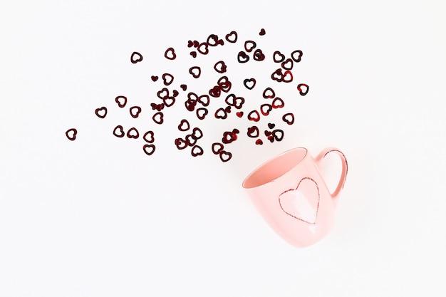 Disposition de la saint-valentin. mug rose avec des coeurs au départ sur un fond blanc. la saint valentin