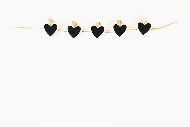 Disposition de la saint-valentin. tableau noir craie coeurs sur des pinces à linge en bois sur ficelle de jute sur blanc