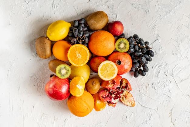 Disposition de sélections de fruits frais à plat sur une surface grunge telle que raisins, kiwi, orange, fruits tropicaux exotiques