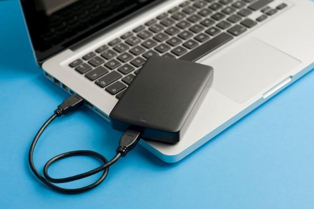 Disque dur externe avec câble noir usb sur tableau bleu pour ordinateur portable