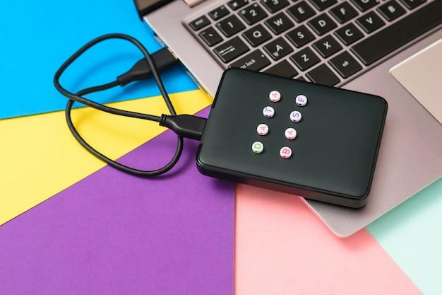 Disque dur externe étiqueté base de données connectée à un ordinateur portable sur fond clair. la vue du haut. le concept de stockage de sauvegarde. mise à plat.