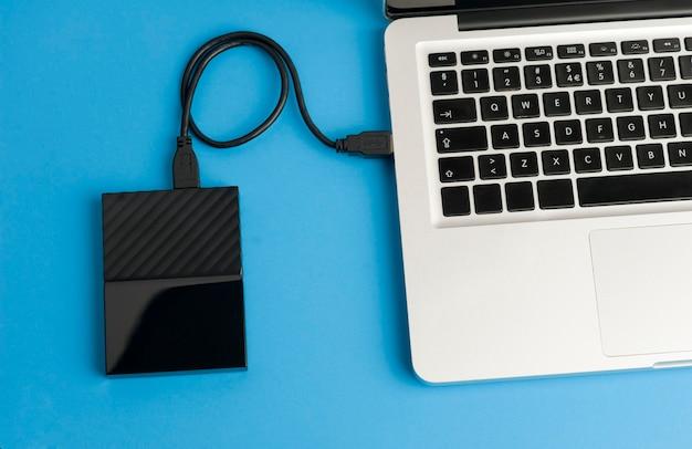 Disque dur externe noir avec câble usb vue partielle de l'ordinateur portable sur la table de bureau bleu vue de dessus