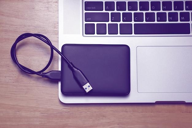 Disque dur externe et ordinateur portable sur fond de bois.