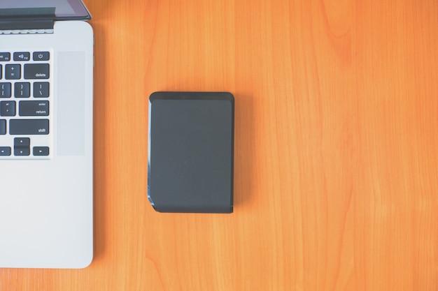Disque dur externe portable sur le bureau près de l'ordinateur portable