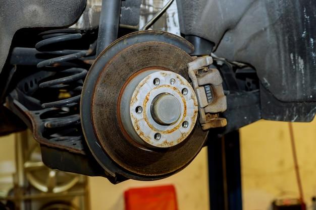 Disque de frein arrière avec étrier partiellement retiré sur le point d'être remplacé