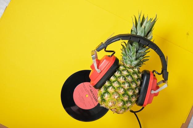 Disque vinyle et ananas dans un casque rétro rouge sur fond jaune, vue de dessus