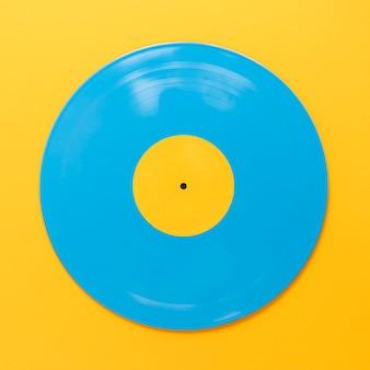 Disque de vinyle bleu plat lay avec fond jaune