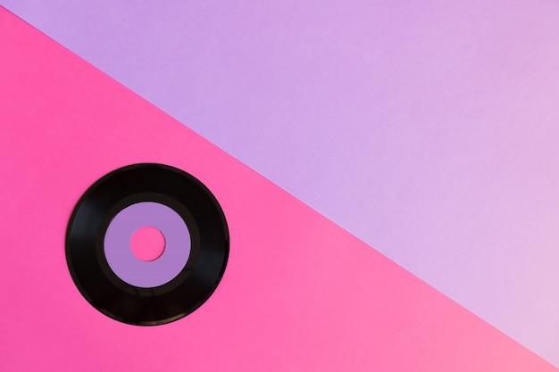 Un disque vinyle obsolète sur un fond de papier de deux tonnes: rose et violet, culture pop.