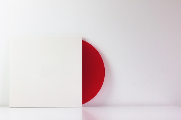 Disque vinyle rouge, dans sa boîte blanche, avec un espace vide pour écrire.