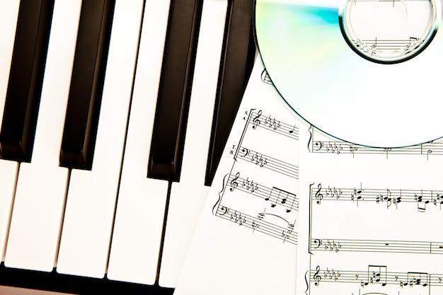 Disques compacts et partitions musicales placées au piano