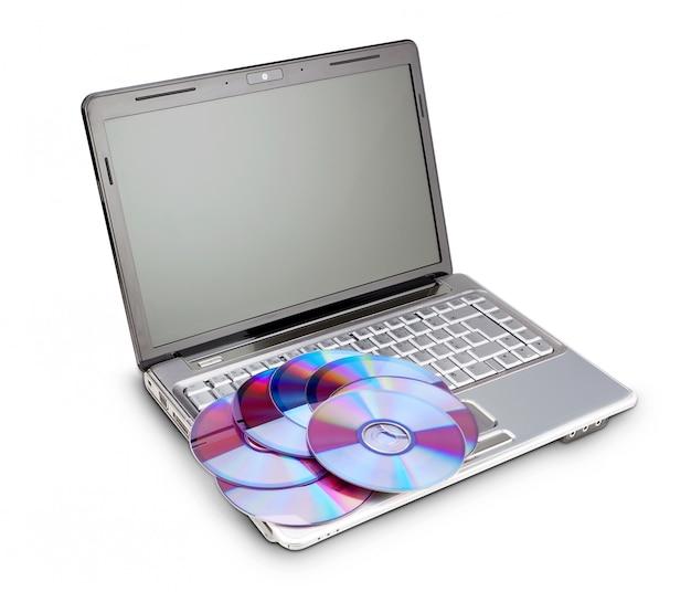 Disques pour enregistrer des données sur un ordinateur portable moderne. sur un mur blanc.