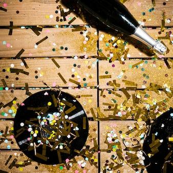Disques vinyles et bouteille de boisson entre des confettis brillants