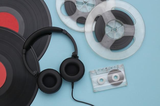 Disques vinyles rétro, bobine magnétique audio, cassette audio et casque stéréo sur fond bleu. vue de dessus. mise à plat