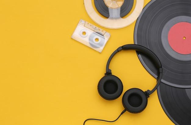 Disques vinyles rétro, bobine magnétique audio, cassette audio et casque stéréo sur fond jaune. espace de copie. vue de dessus