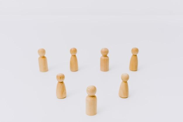 Distance sociale symbolisée par des figures en bois isolées les unes des autres sur fond blanc.
