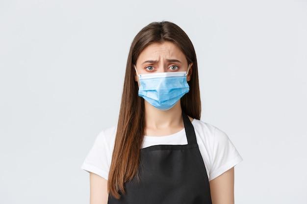 Distanciation sociale de covid-19, employés de café, cafés et concept de coronavirus. barista mignon sombre et triste, caissier en tablier noir et masque médical grimaçant déçu ou troublé.