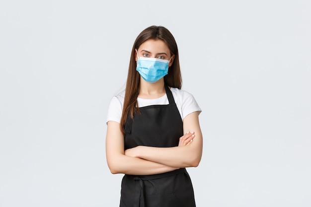 Distanciation sociale de covid-19, employés de café, cafés et concept de coronavirus. barista sérieux et confiant travaillant dans un masque médical pour empêcher la propagation des maladies virales pendant la pandémie.