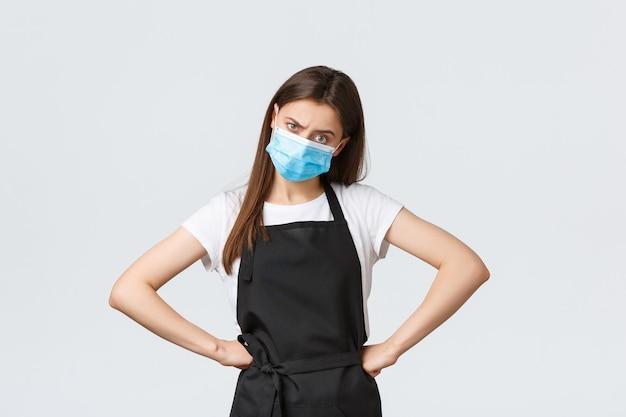 Distanciation sociale de covid-19, employés de café, cafés et concept de coronavirus. gérant de magasin mécontent et sérieux en tablier noir et masque médical fronçant les sourcils et semblant frustré