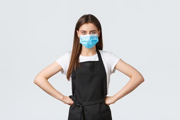 Distanciation sociale de covid-19, employés de café, cafés et concept de coronavirus. gestionnaire dans l'épicerie debout autoritaire avec les mains sur la taille, portant un masque médical, suivez le protocole de prévention des virus.