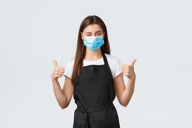 Distanciation sociale de covid-19, employés de café, cafés et concept de coronavirus. un joli barista confiant dans un masque médical fait un clin d'œil et montre le pouce levé, assure que toutes les mesures de prévention des virus sont suivies.