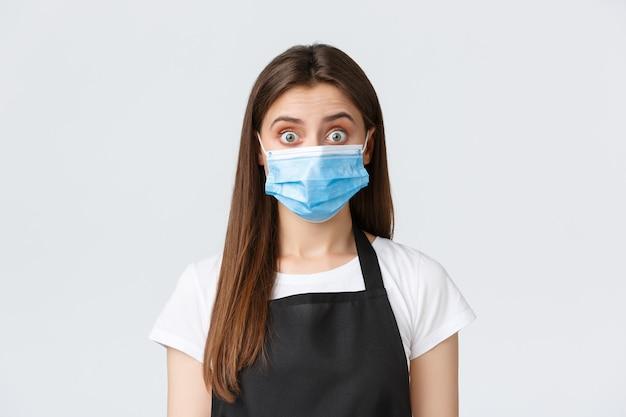 Distanciation sociale de covid-19, employés de café, cafés et concept de coronavirus. une jolie barista brune choquée et surprise portant un masque médical écarquille les yeux en entendant des potins ou de grandes nouvelles