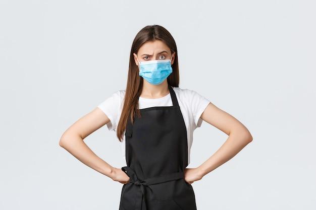 Distanciation sociale covid-19, employés, cafés et concept de coronavirus. barista à l'air sérieux mécontent, employé en tablier noir et masque médical réprimandant la personne pour ne pas avoir utilisé de désinfectant pour les mains