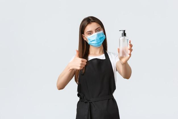 Distanciation sociale de covid-19, employés, cafés, concept de coronavirus. barista ou serveuse portant un masque médical montrant un désinfectant pour les mains et le pouce levé pour s'assurer que toutes les mesures de prévention des virus sont suivies
