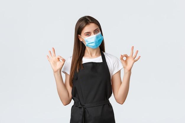 Distanciation sociale covid-19, employés, cafés et concept de coronavirus. vendeuse sérieuse et confiante en tablier noir et masque médical montrant un geste correct sans problème, garantie de qualité de service