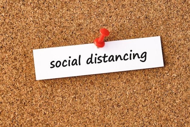 Distanciation sociale. mot écrit sur un morceau de papier ou une note, panneau de liège.