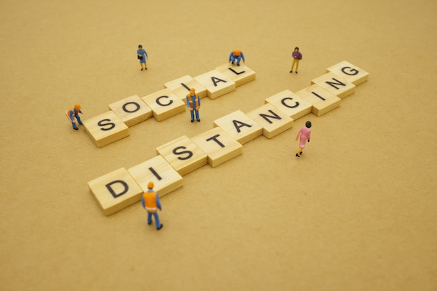 Distanciation sociale. les personnes miniatures restent séparées pour réduire l'infection par le virus covid 19. maintenir une distance sociale