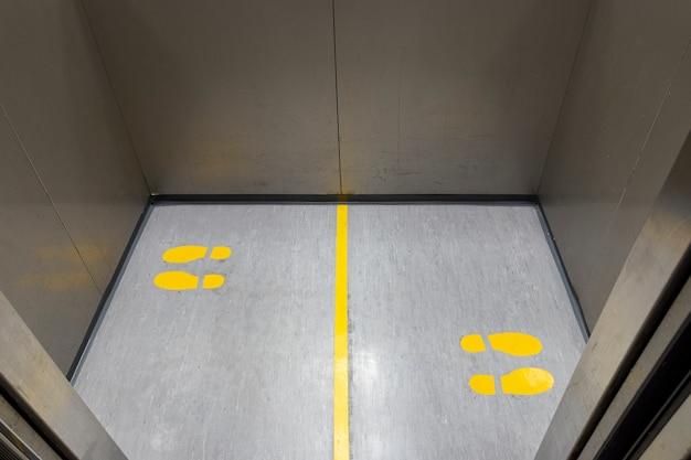 Distanciation sociale pour covid19 avec signe d'empreinte jaune dans l'ascenseur public