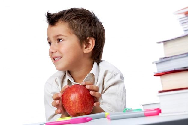 Distrait petit garçon jouant avec sa pomme