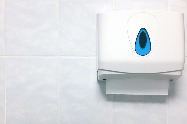 Distributeur d'essuie-mains en papier flou sur un mur de granit dans la salle de bain