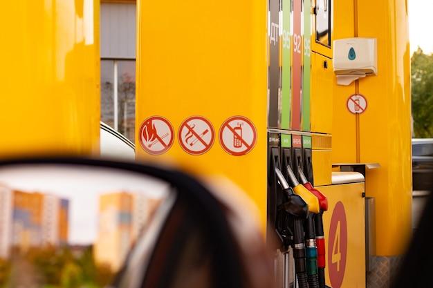 Distributeur jaune dans une station-service avec différents types d'essence, vue depuis la fenêtre de la voiture