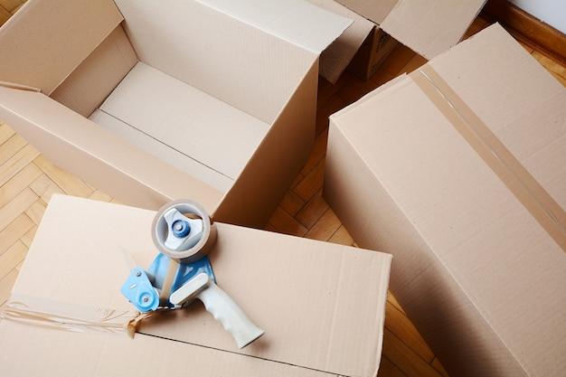 Distributeur de ruban adhésif scellant une boîte en carton d'expédition