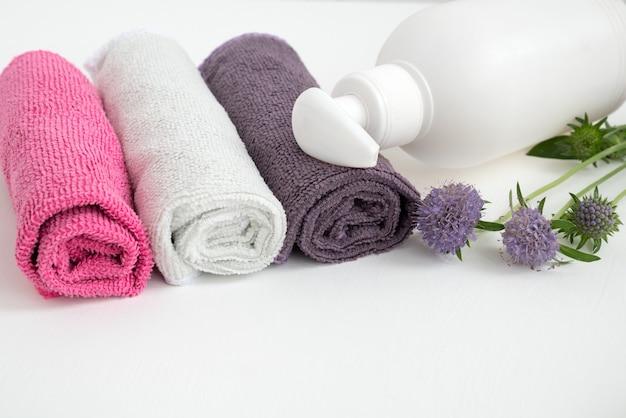 Distributeur de savon avec fleur violette en fleurs avec serviettes colorées roulées sur table de salle de bain