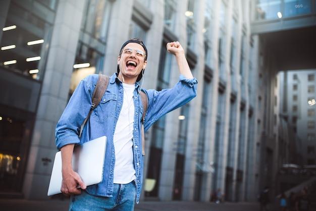 Dites bonjour homme heureux rencontrant quelqu'un homme heureux écoutant de la musique avec des écouteurs depuis un smartphone