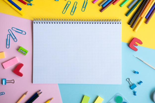 Divers accessoires scolaires sur tableau de couleurs avec espace de copie. concept de retour à l'école.