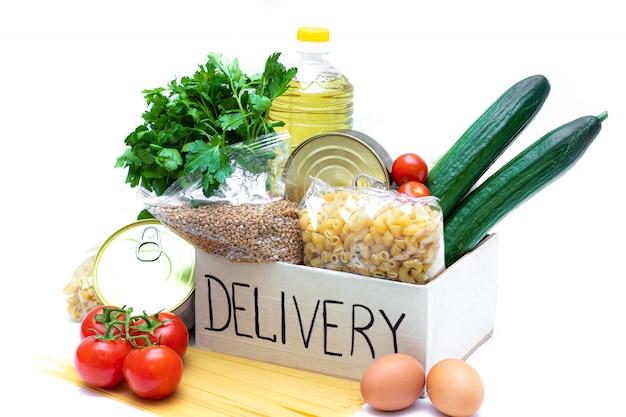 Divers aliments en conserve, pâtes et céréales dans une boîte en carton.